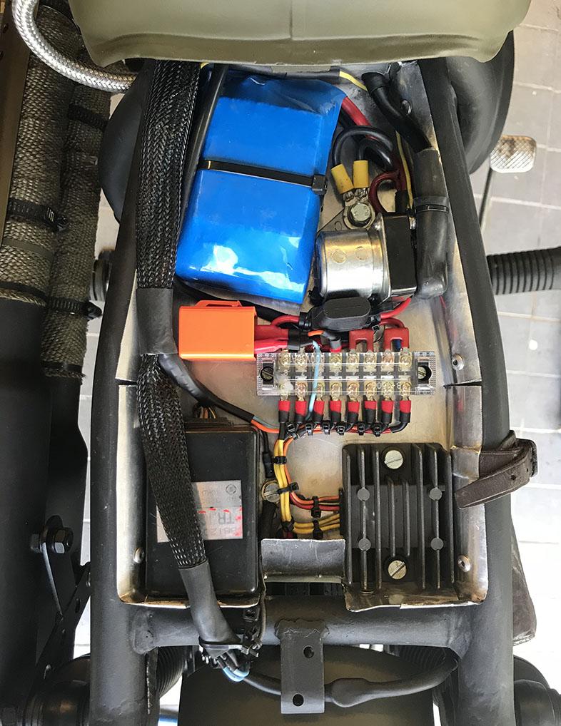 Elen och batteri kopplad under sätet på scrambler